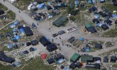 """An aerial view shows a field named """"new jungle"""" with tents and makeshift shelters where migrants and asylum seekers stay in Calais"""