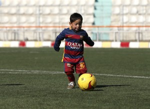 Five year-old Murtaza Ahmadi wears a shirt of Barcelona's star Lionel Messi as he plays soccer at the Afghan Football Federation headquarters in Kabul