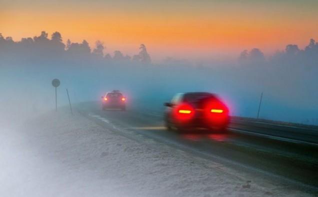 15039932 - rear lights of car on road in dark foggy winter evening