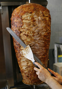 A worker cuts meat from a spit in a Kebab restaurant in Dortmund