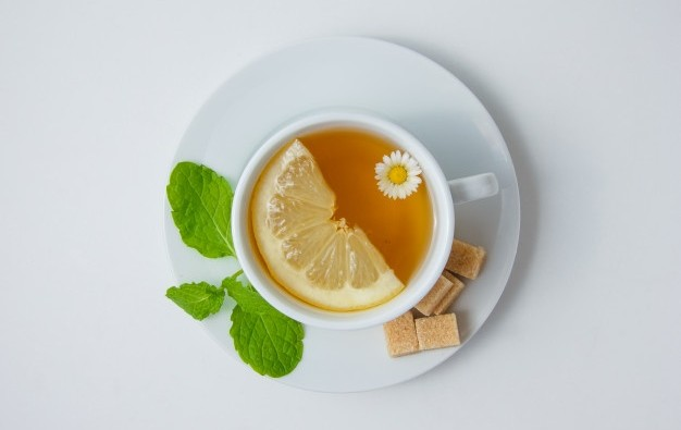 top-view-cup-chamomile-tea-with-lemon-mint-leaves-sugar-white-surface-horizontal_176474-5080